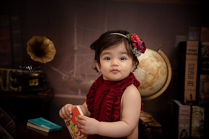baby girl cute holding book back study backdrop indoor studio professional photo session Meghna Rathore Photography Delhi