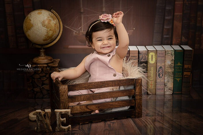 baby girl sitting in wooden box smiling professional photo shoot Meghna Rathore Photography
