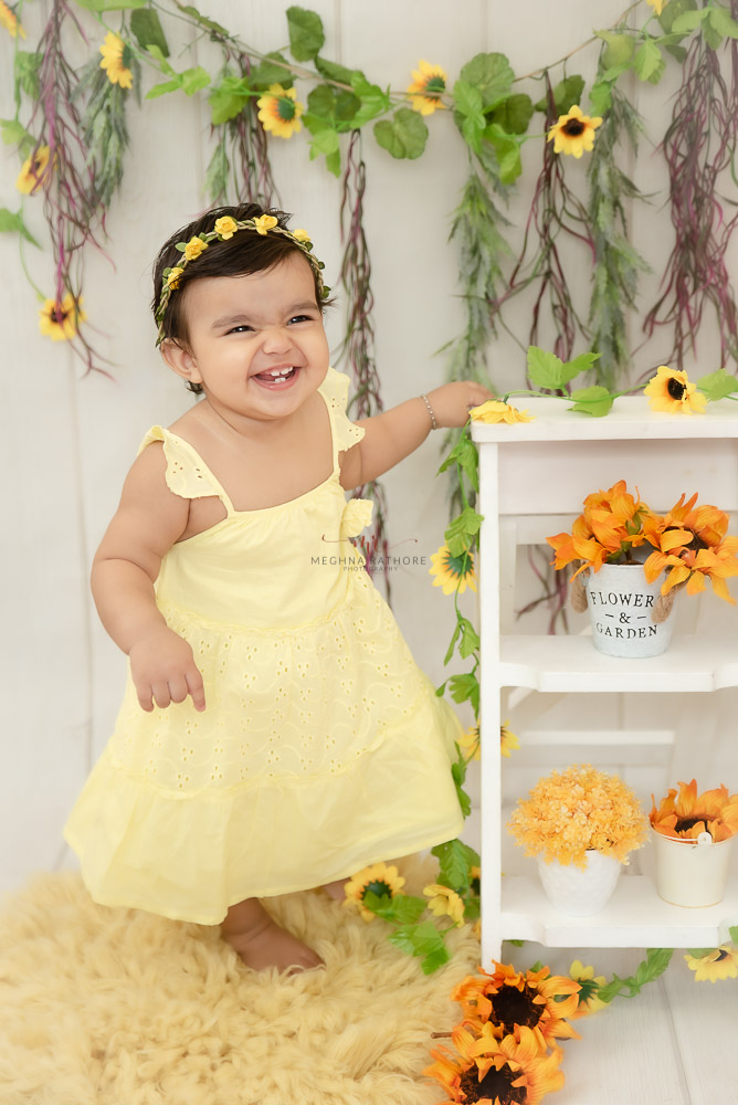 baby girl yellow dress smiling floral and props decoration Meghna Rathore Photography