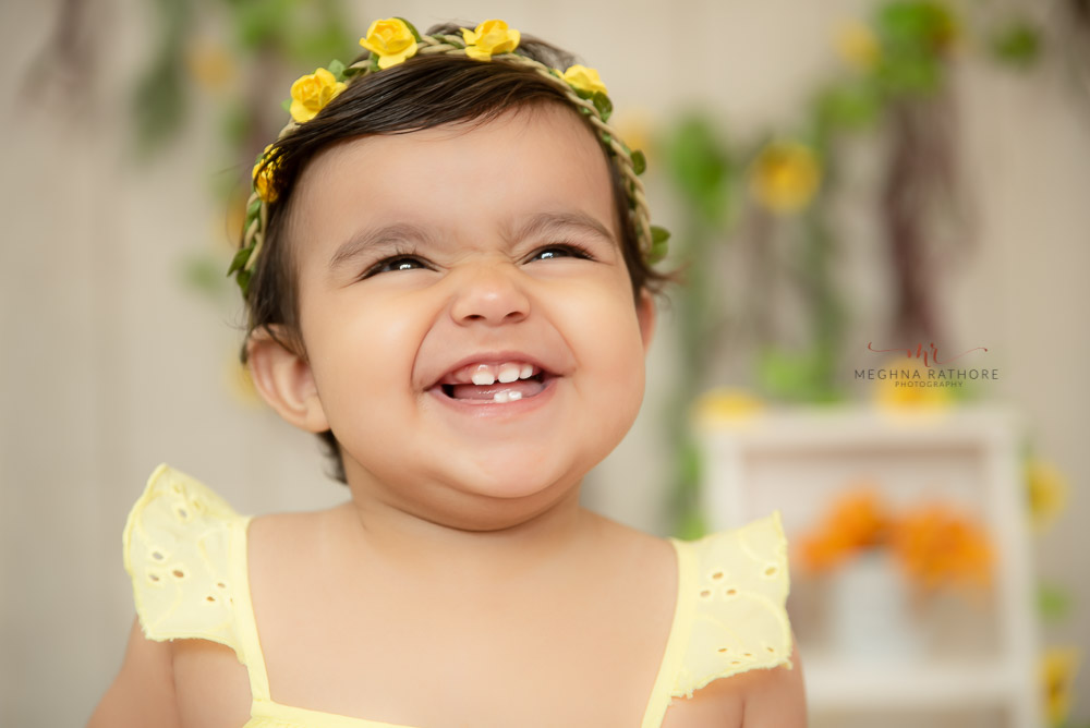 baby girl in yellow dress laughing close up professional studio delhi photo shoot Meghna Rathore Photography