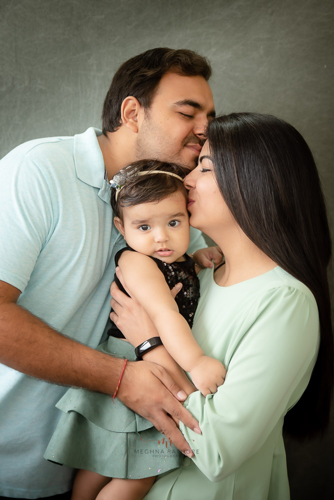 cute family pose papa kissing mom and holding baby girl arms indoor studio delhi gurgaon Meghna Rathore Photography