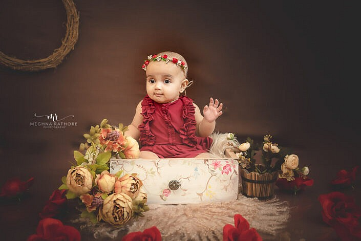 baby girl in red dress in floral decoration brown backdrop professional photo shoot Meghna Rathore Photography