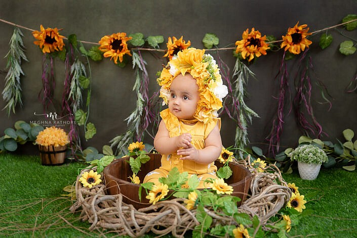 Baby in yellow dress professional photo shoot sitting in bucket grass carpet Meghna Rathore Photography