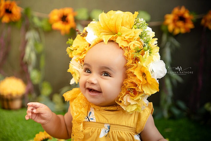 baby photo shoot close up smiling yellow head cap flower backdrop Meghna Rathore Photography