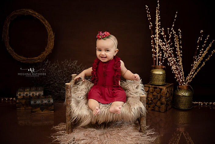 baby girl smiling wooden bed props decoration professional baby photo shoot Meghna Rathore Photography