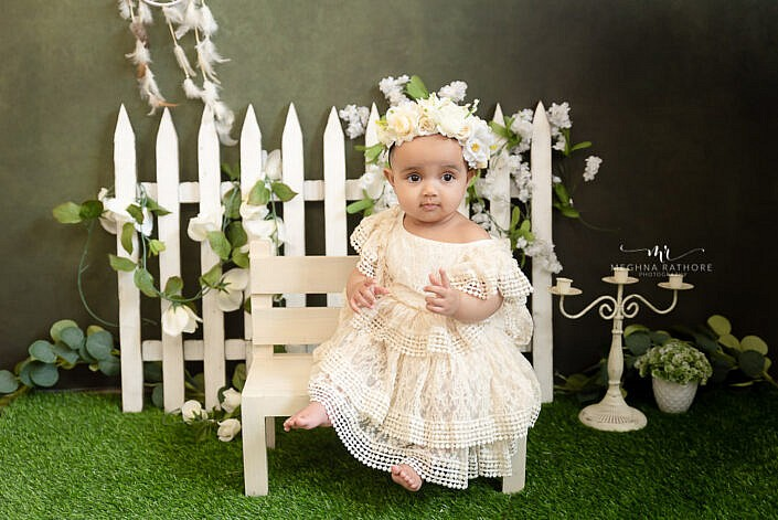 baby girl in white dress with white flower hand band Meghna Rathore Photography Delhi