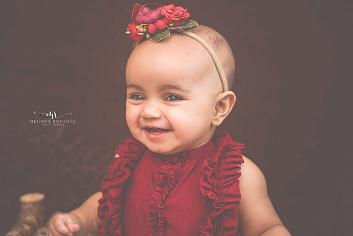 baby girl smiling red head band cure photo shoot props Meghna Rathore photography