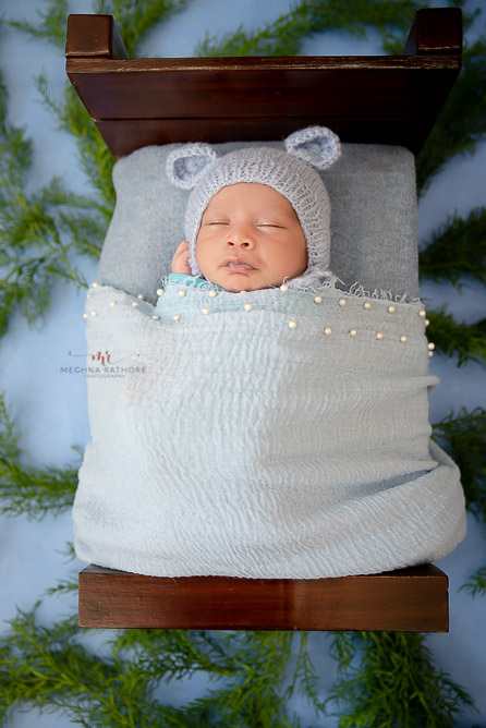 baby in below dress wooden bed blue backdrop photo shoot by Meghna Rathore Photography