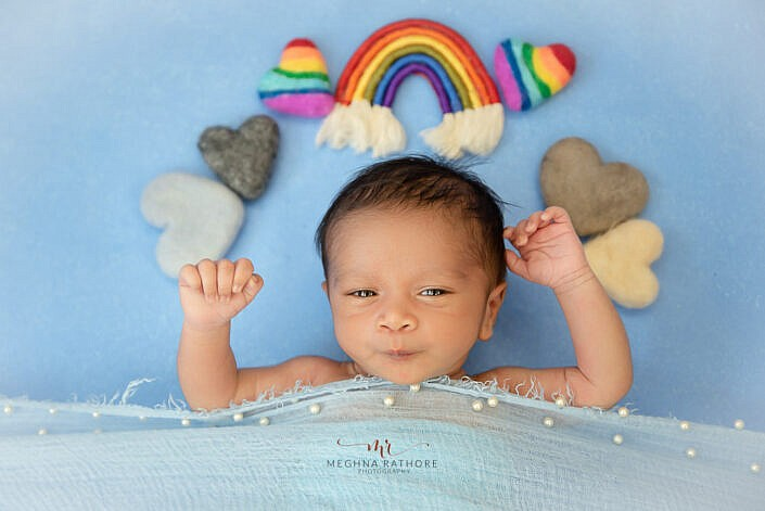 newborn photo shoot lying on blue backdrop rainbow and heart props by Meghna Rathore Photography