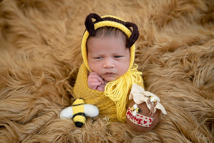 baby in potato sack pose in yellow dress brown fur Meghna Rathore Photography