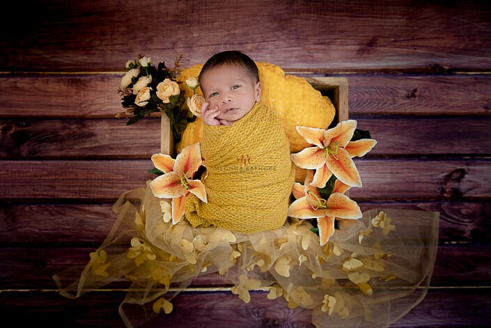 newborn photo shoot baby wrapped in yellow wrap lying in basket wooden backdrop