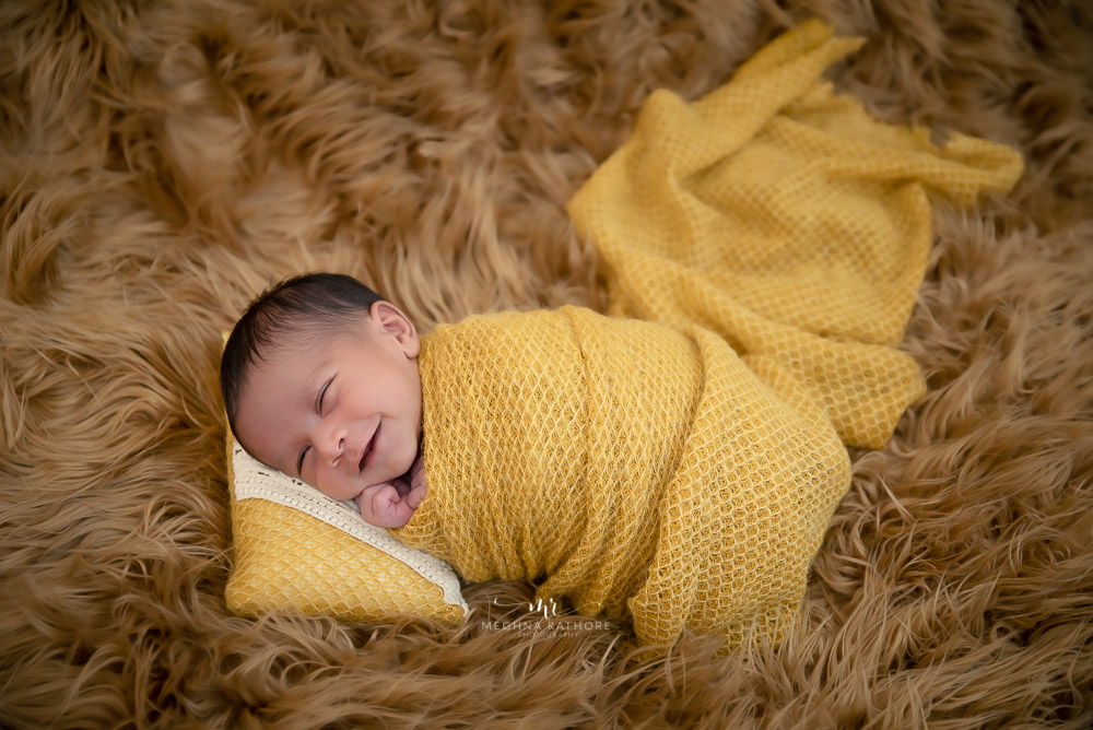 newborn photo shoot wrapped in yellow cloth lying on brown fur prop Meghna Rathore Photography indoor photo shoot