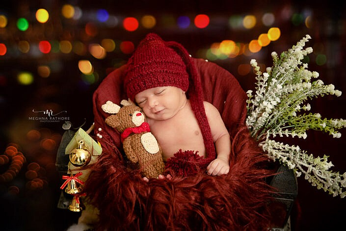 newborn wearing red hat with red cloth behind sitting with a small teddy bear and leaves decoration and twinkling lights in backdrop photo shoot by Meghna Rathore Photography
