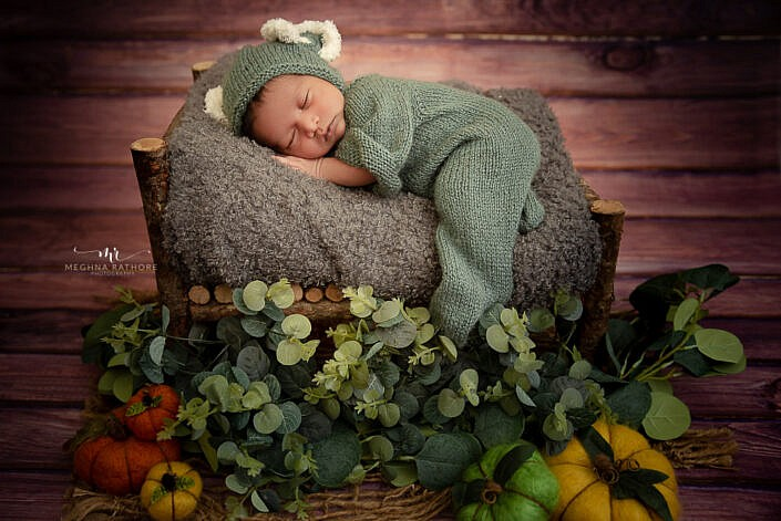 baby in green dress wooden bed leaves decoration Meghna Rathore Photography newborn photo shoot