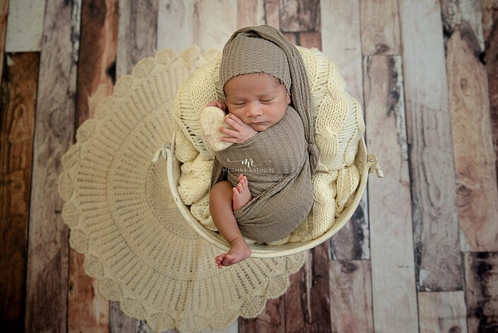 baby in white bucket wooden backdrop photo shoot wrapped in wrap Meghna Rathore Photography