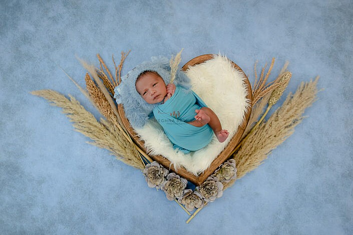 newborn baby lying in wooden bowl with decoration around and wrapped in blue cloth with blue backdrop photo shoot by Meghna Rathore Photography