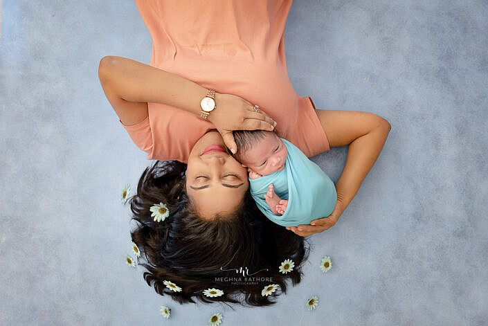 newborn wrapped in blue dress lying with mom on blue backdrop with flower decoration photo shoot by Meghna Rathore Photography