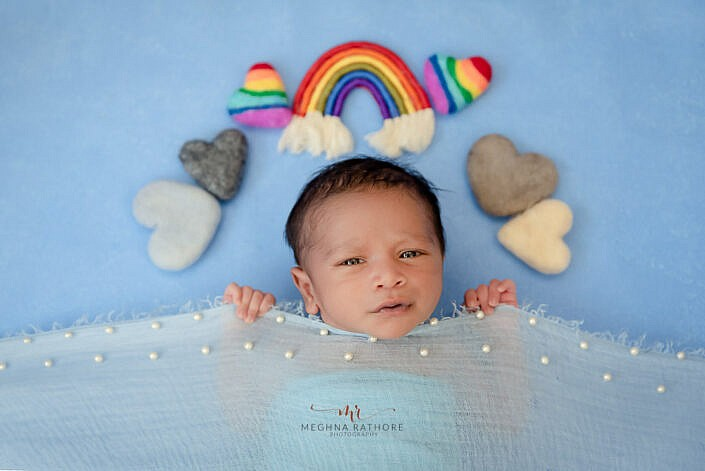 newborn baby holding onto the blue cloth with blue backdrop and small props of heart and rainbow photo shoot by Meghna Rathore Photography