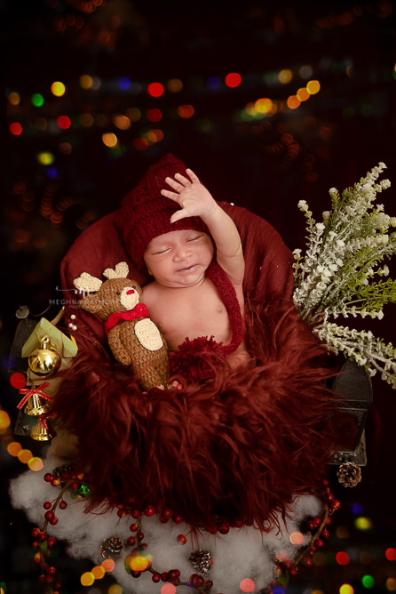 newborn baby wearing red hat decoration around photo shoot by Meghna Rathore Photography