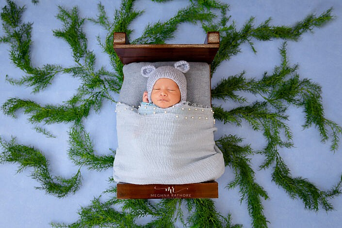newborn sleeping on bed wrapped in blue dress blue backdrop leaves decoration photo shoot by Meghna Rathore Photography