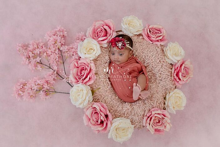 newborn wrapped in pink cloth lying in a basket with flower decoration of pink and white color photo shoot by Meghna Rathore Photography
