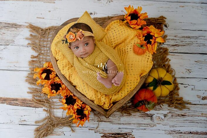newborn lying in heart bowl wrapped in yellow cloth wooden backdrop photo shoot by Meghna Rathore Photography