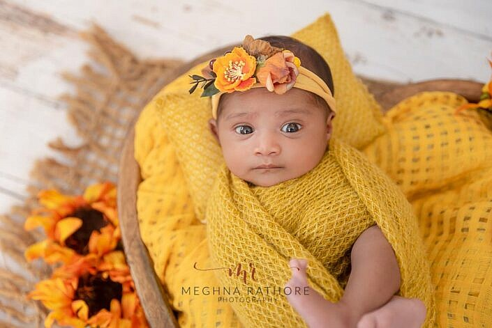 baby photo shoot eyes wide open wrapped in yellow cloth by Meghna Rathore Photography