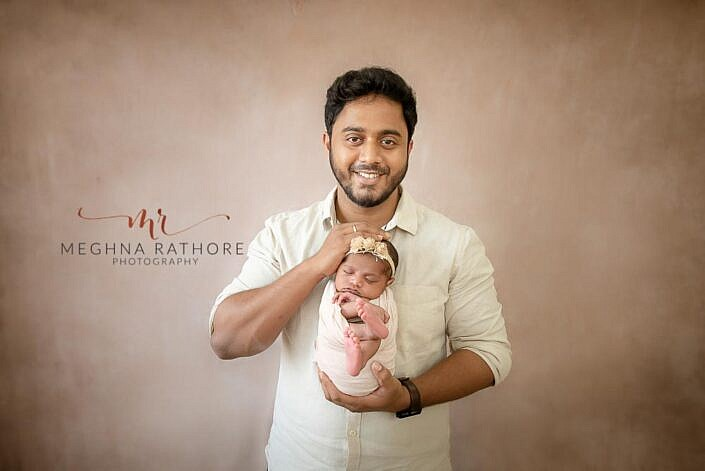 father holding newborn in wrapped pose brown backdrop by Meghna Rathore Photography