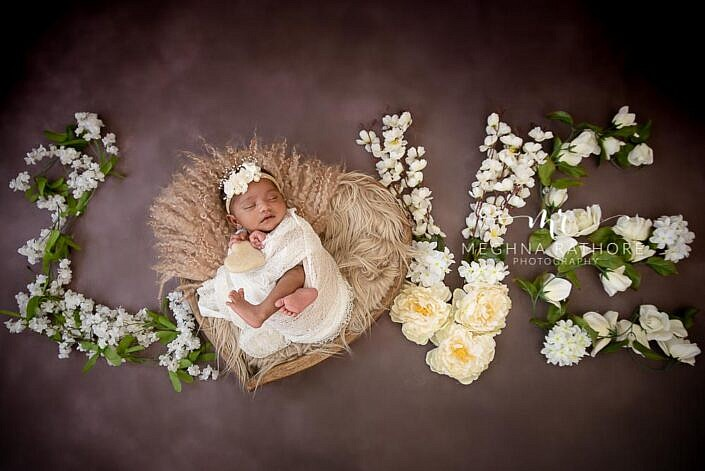 newborn posing in heart bowl, love written with white flowers brown backdrop photo shoot by Meghna Rathore Photography