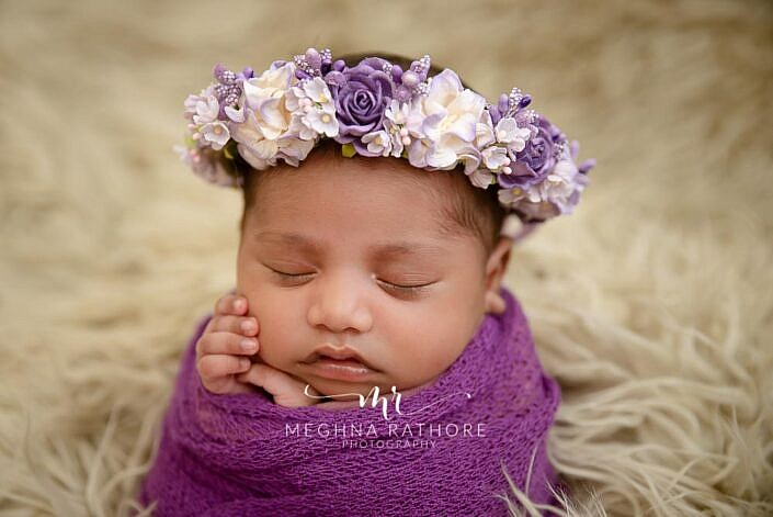 newborn in potato sack pose wrapped in purple cloth with matching purple white headband photo shoot by Meghna Rathore Photography