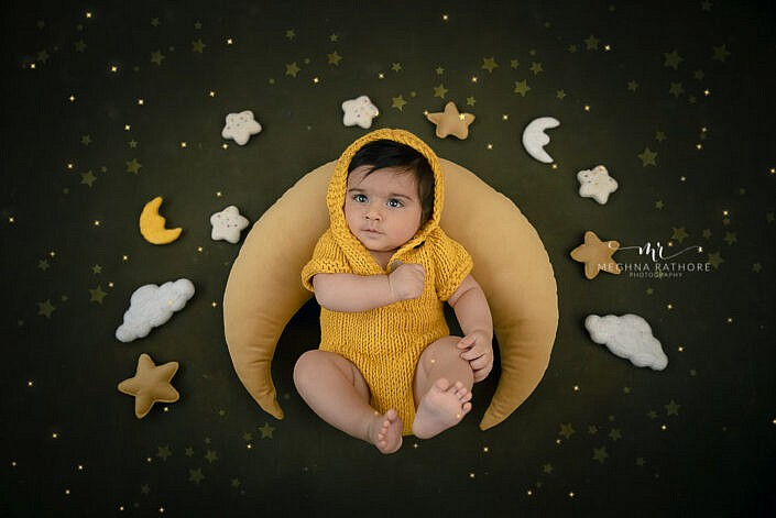 newborn baby in yellow knit dress lying on moon prop pillow green backdrop photo shoot by Meghna Rathore Photography