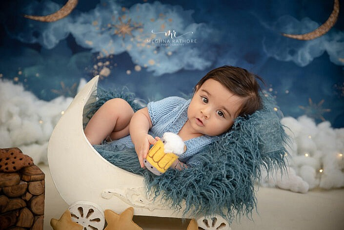 newborn baby wearing blue knit dress lying in a wood wagon prop blue backdrop photo shoot by Meghna Rathore Photography
