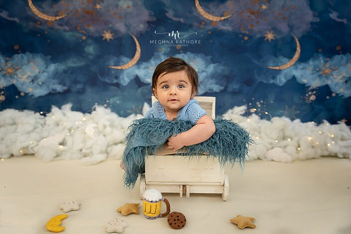 newborn baby in a blue dress sitting in a wood prop with cloud and moon backdrop photo shoot by Meghna Rathore Photography