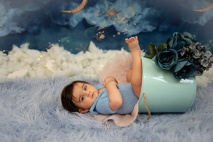 newborn baby in a blue bucket wearing a blue knit dress photo shoot by Meghna Rathore Photography