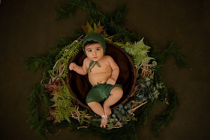 newborn baby wearing green dress lying in a basket with leaves decoration and brown backdrop photo shoot by Meghna Rathore Photography
