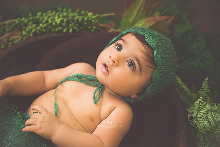 newborn baby dressed with a green cap looking up photo shoot by Meghna Rathore Photography