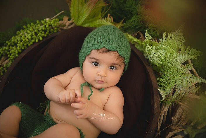 newborn baby with a green cap leaves decoration photo shoot by Meghna Rathore Photography
