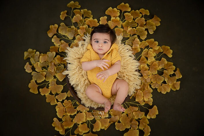newborn baby dressed in yellow surrounded by red yellow leaves photo shoot by Meghna Rathore Photography