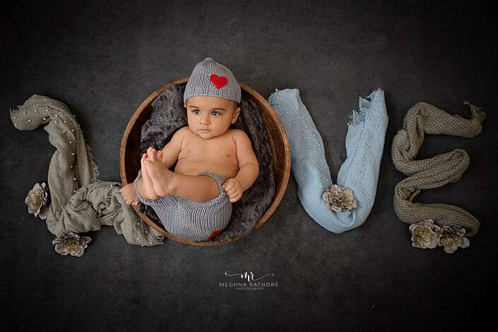 newborn baby lying in a wood basket in LOVE symbol photo shoot by Meghna Rathore Photography