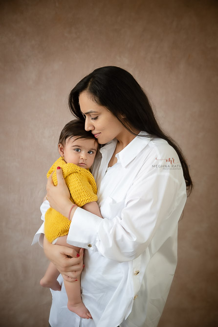 mom holding baby in her arms photo shoot by Meghna Rathore Photography