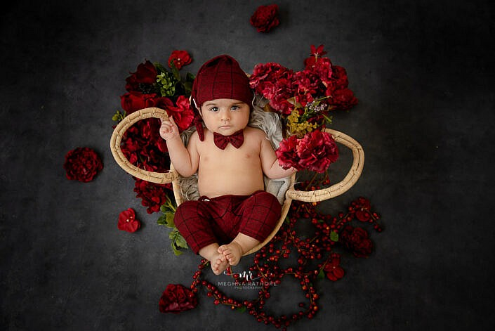 newborn baby lying in a basket with red cherry flower decoration in grey backdrop photo shoot by Meghna Rathore Photography