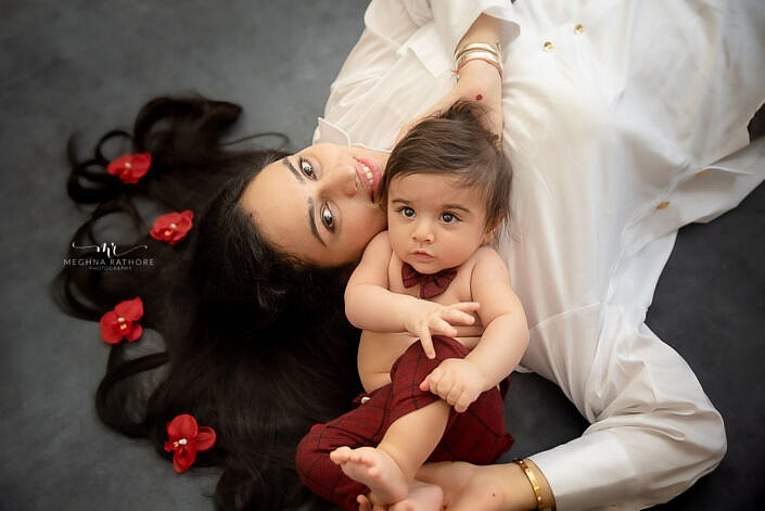 baby lying with her mother with flower decoration on grey backdrop photo shoot by Meghna Rathore Photography