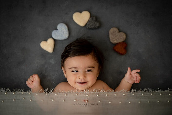 newborn baby smiling lying on a grey backdrop with heart shape prop photo shoot by Meghna Rathore Photography