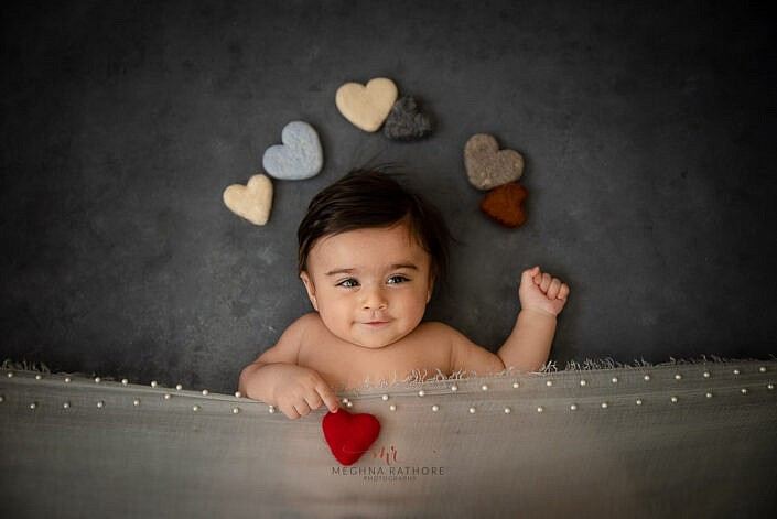 newborn baby smiling with brown cloth cover and grey backdrop with hearth prop photo shoot by Meghna Rathore Photography