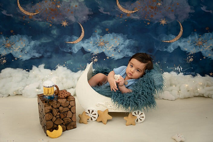 newborn baby lying in a wooden prop wagon with other decorations around photo shoot by Meghna Rathore Photography