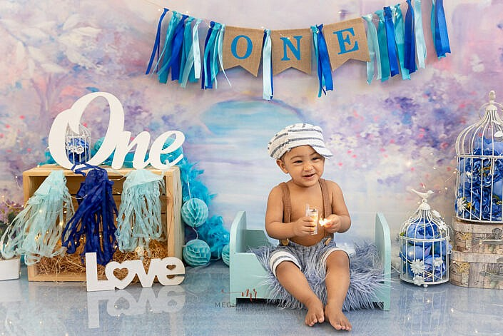 boy kid sitting on blue bed on a blue fur one and love prop wood box purple print backdrop photo shoot by Meghna Rathore Photography gurgaon