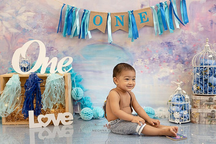 boy kid wearing cute dress one and love prop flower and small cage decoration flower backdrop photo shoot by Meghna Rathore Photography gurgaon