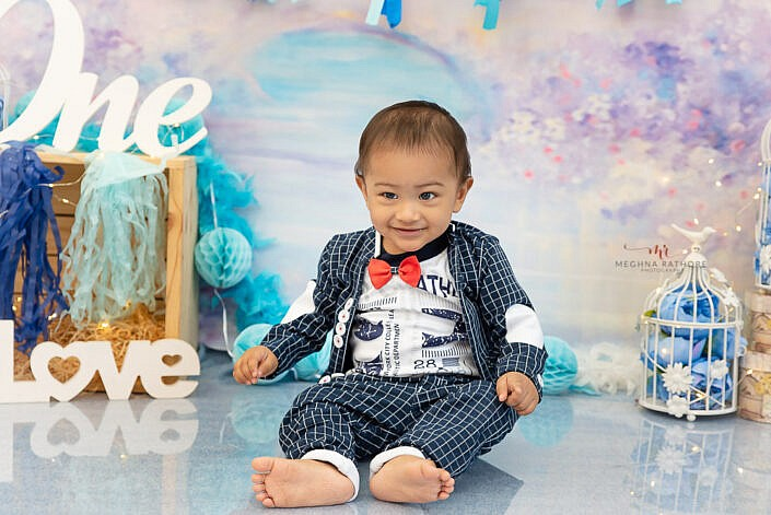 boy kid wearing suit dress wearing flower backdrop one and love wood prop blue shining floor photo shoot by Meghna Rathore Photography Delhi