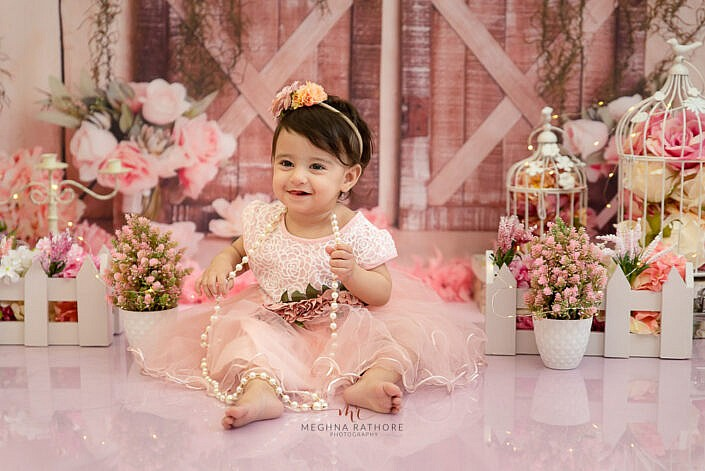 girl kid wearing peach dress with a necklace flower decoration pink shining floor backdrop photo shoot by Meghna Rathore Photography delhi