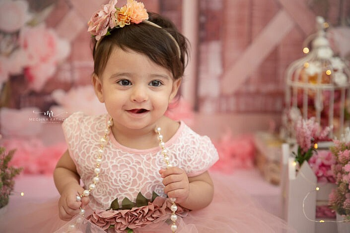 one year old girl kid wearing pink dress with pink backdrop photo shoot by Meghna Rathore Photography gurgaon
